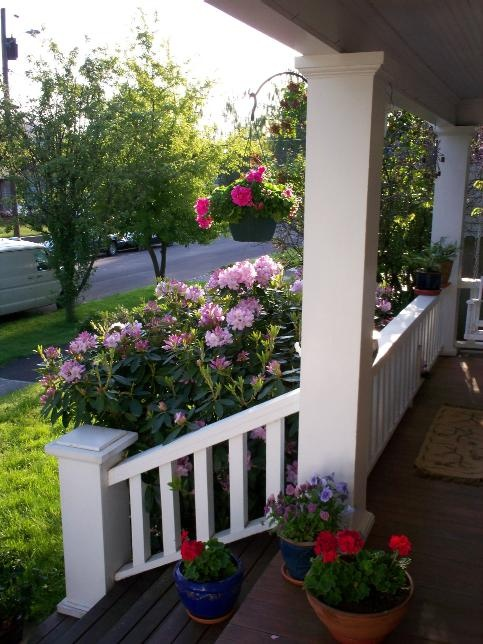 Front porch w/ hanging baskets and rhododendrums -just like my mom's.