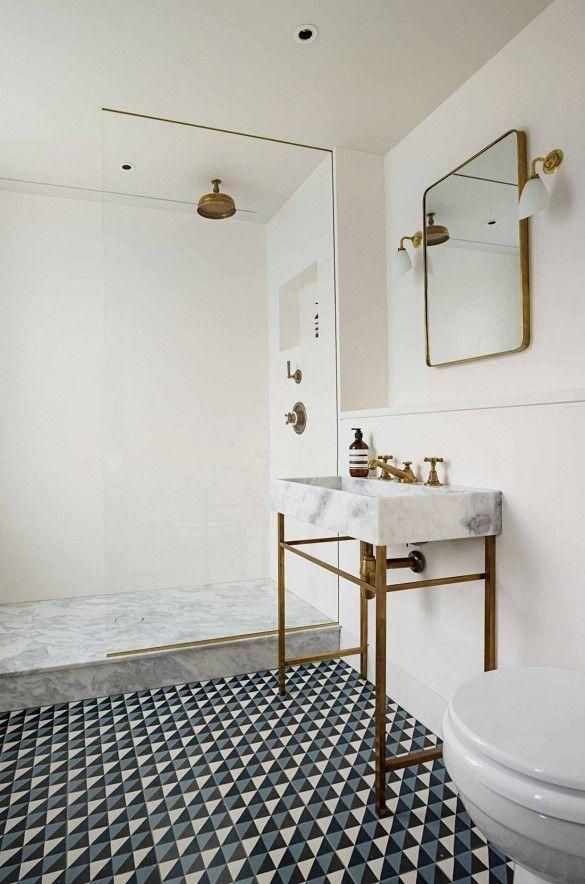 Geometric triangle tiled bathroom floor with marble and brass sink, tiny sconces, and walk up marble rain shower. Stunning mix of traditional glamour and contemporary minimal design.