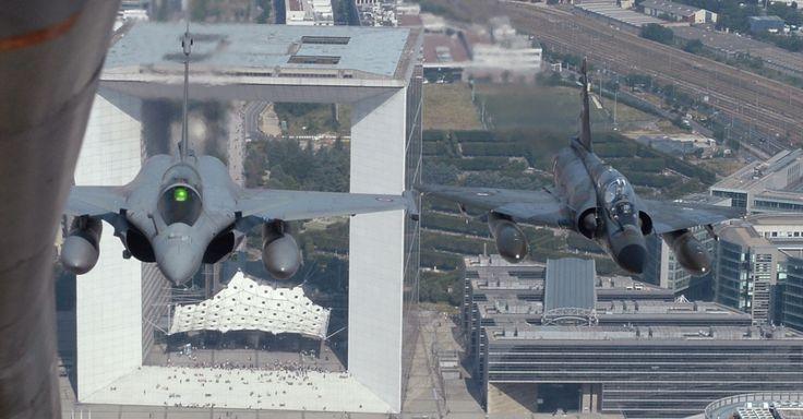 Foto tirada a partir de um Boeing C135 mostra um caça Rafale francês (à esq.) e um caça Mirage sobrevoando a cidade de Paris, na França, durante o desfile do Dia da Bastilha Boris Horvat/AF