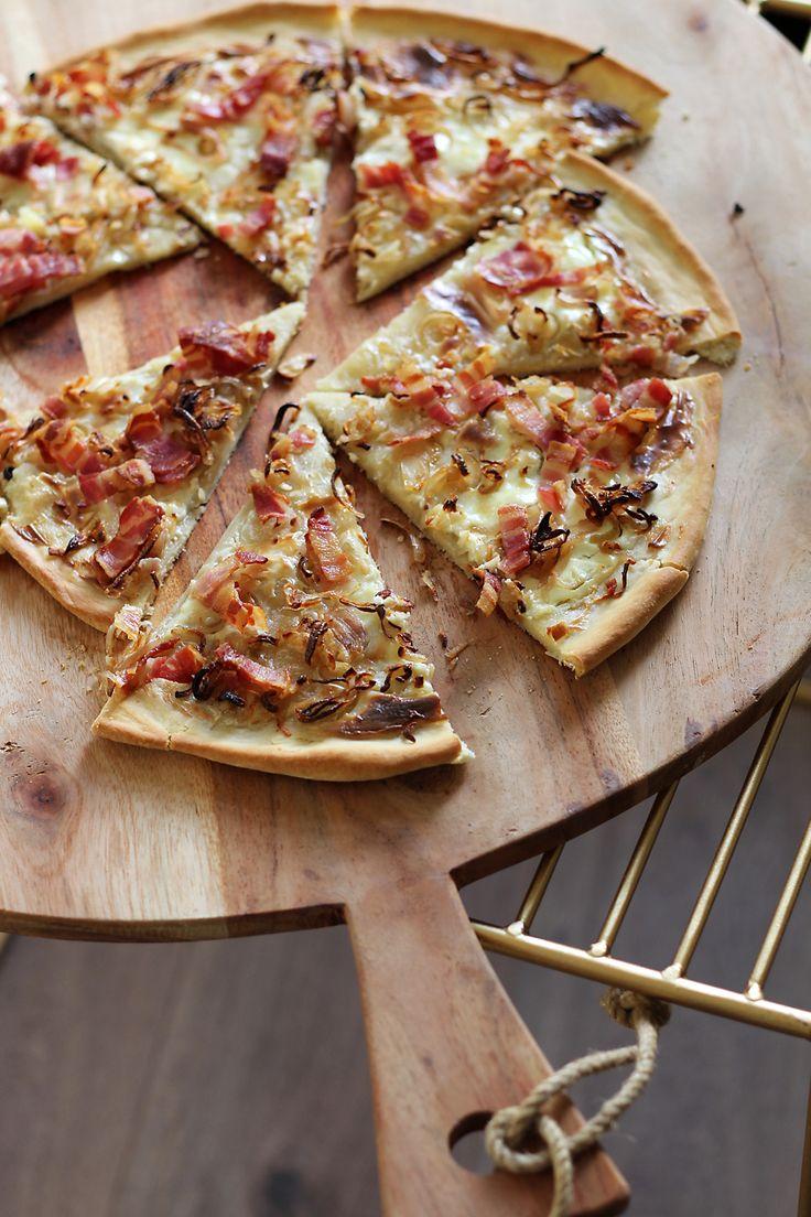 Een klassieker uit de Elzas: flammkuchen met crème fraîche, ui en spekjes. Deze zie je vaak als een vierkante, ovalen of rechthoekige plaatpizza, maar wij waren rebels en bakten lekker een rond exemplaar. Verwarm je oven voor op 230 graden en zet je pizzaplaat of bakplaat erin, zodat deze alvast heet kan worden. Leg de pizzabodem op een …