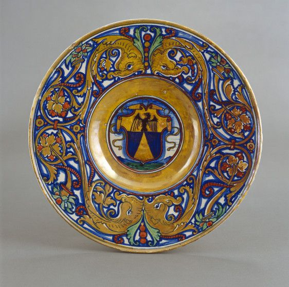 "Workshop of Maestro Giorgio Andreoli of Gubbio, 1465/1470- 1553. Italian maiolica, 1524, ""Plate with border of foliate scrollwork with dolphin heads and cornucopias, in the center, shield of arms of Vigerio of Savona."