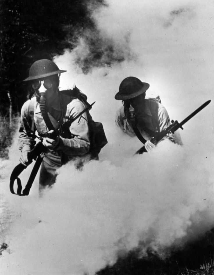 British troops in a cloud of gas. WW1. Not British troops. Rank stripe upsidedown. Maybe a staged picture, shirts too clean.