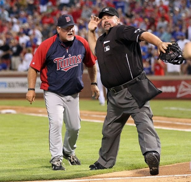 Manager Ron Gardenhire of the Minnesota Twins is ejected by home plate umpire Wally Bell after arguing about his pitcher Scott Diamond being ejected for throwing the ball over the head of Josh Hamilton of the Texas Rangers on August 23, 2012 at the Rangers Ballpark in Arlington in Arlington, Texas.