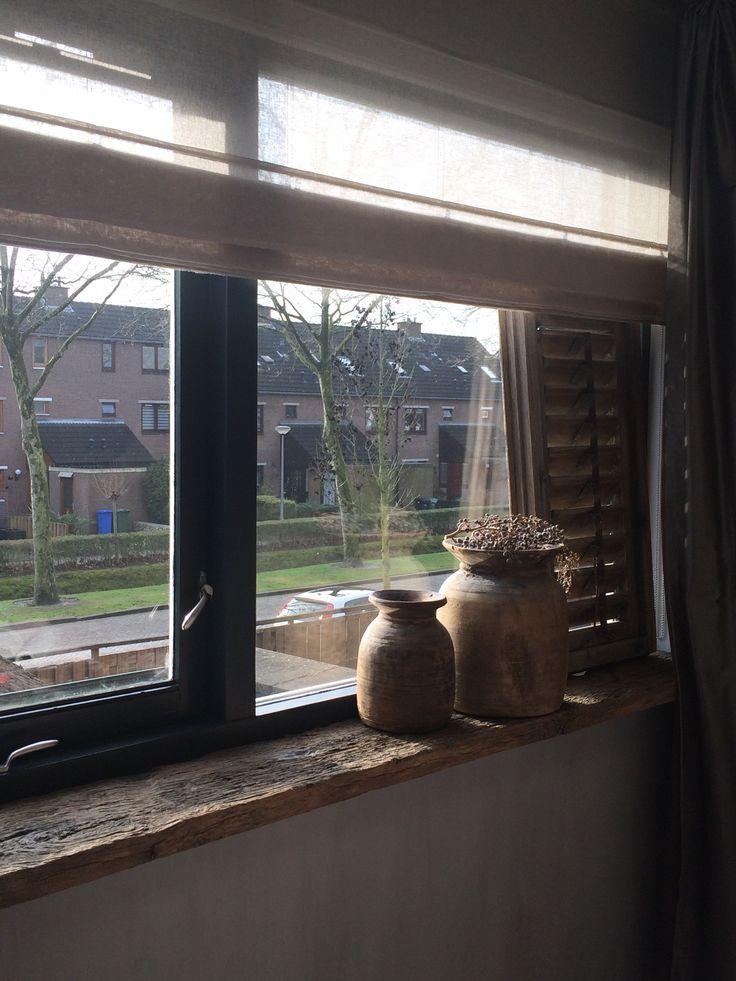 Decoratie in slaapkamer. Blinds, oude vensterbank en zwarte kozijnen.