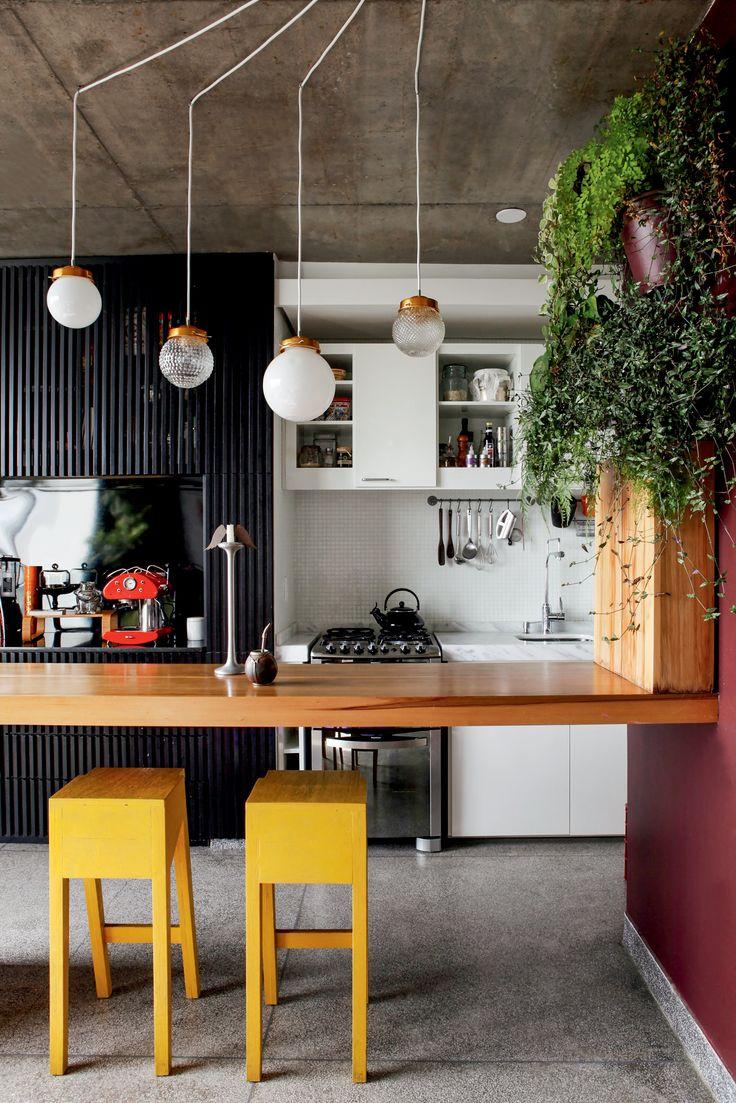 Cozinha com ar vintage: cúpulas transformadas em pendentes, piso de granitina, pastilhas na parede e armário ripado