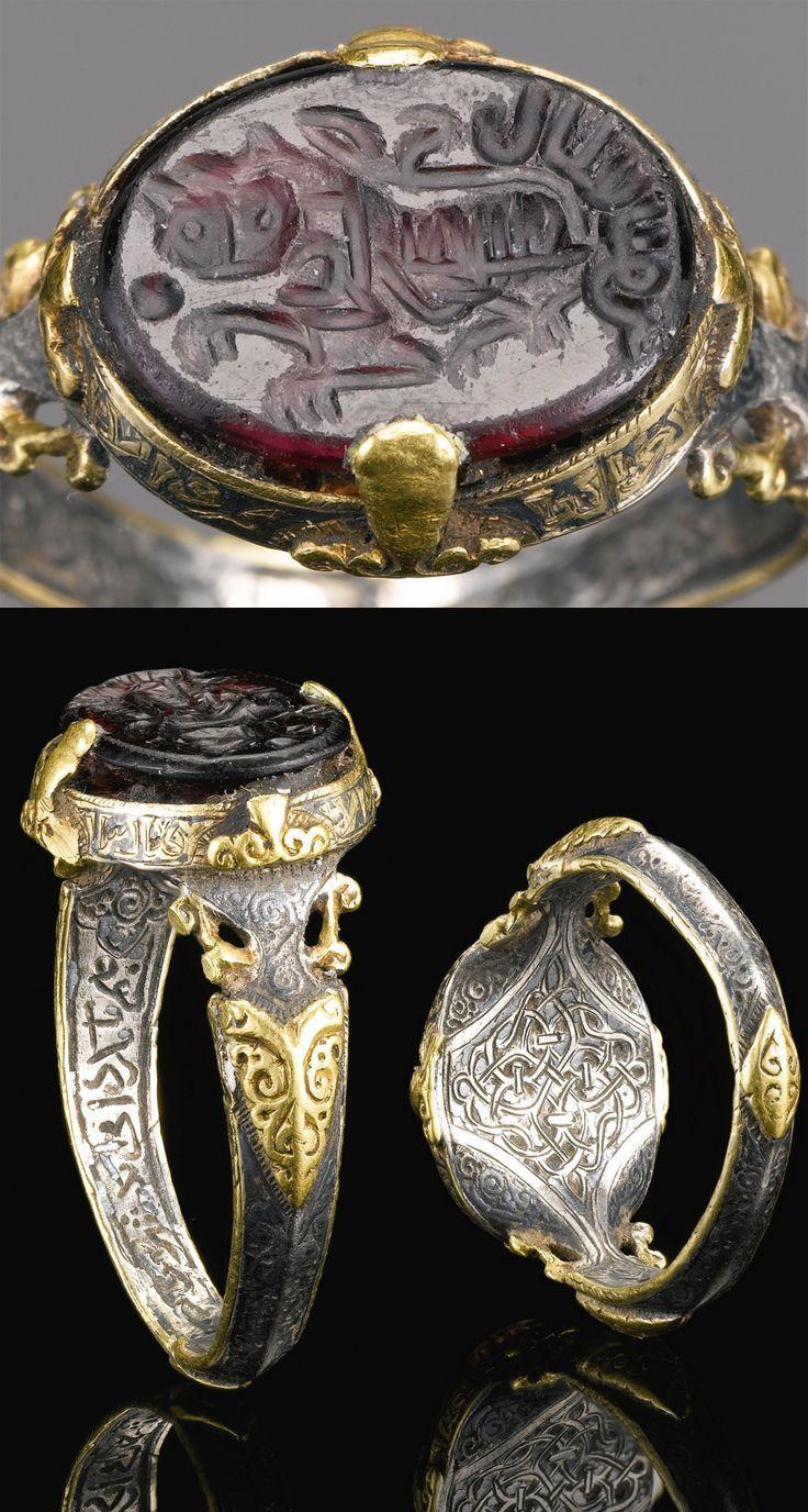 Un selyúcida anillo de plata y oro fino y especial establecido con un profundo sello de piedra púrpura que lleva el nombre de Ali Ibn Yusuf, Persia, siglo 12  el anillo de plata y oro de la decoración, con una banda caligráfica de diseño de interiores y niello a la parte inferior, con una piedra tallada de color morado oscuro con un león y la inscripción  de 2,5 cm. diam.