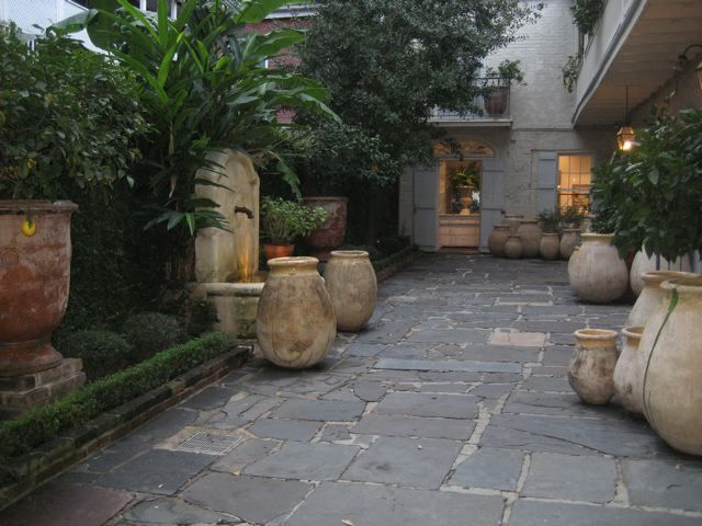 French Olive Jars, courtyard garden. Love the shutters & the house color.