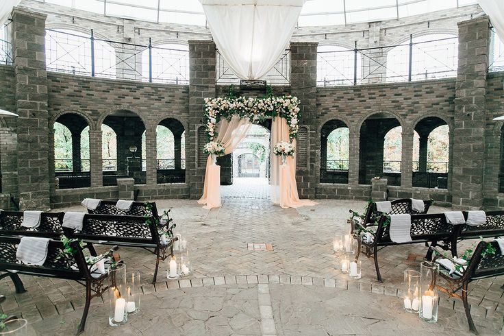 Wedding ceremony in a stone castle, with a high flower arch, compositions in peach shades, a light peach-colored cloth and candles