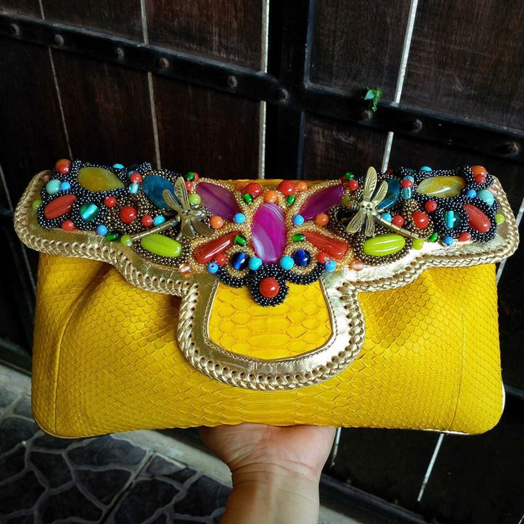 Python leather clutch with real germ stone. Made in Bali... Really nice quality of clutch. It comes in many colors, also shoulder strap. Interest to buy drop me a comment below or send me an email at meiradewi@gmail.com or simply check out collection on balinesian ethnic purses Facebook