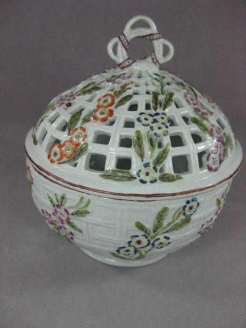 """A rare Derby chestnut basket and lid and having a moulded basket base with trailing flowers and the pierced lid having similar decoration and with a """"lifebuoy"""" type of finial. Unmarked  Circa  1765  Width & height  5 1/2"""""""