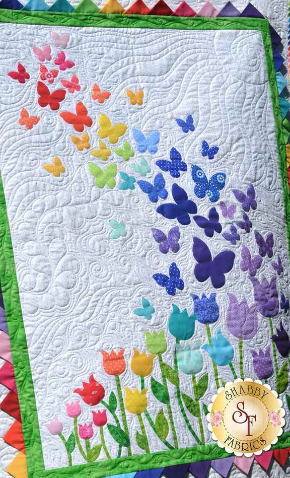 """Butterflies floating over a bed of tulips, finished with bright prairie points for the inner border. Finishes to 40½"""" x 51½""""."""