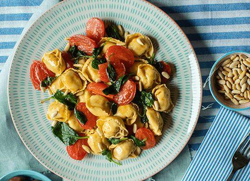 Tortellini Feta e olive Kalamata con pomodori, spinaci e pinoli