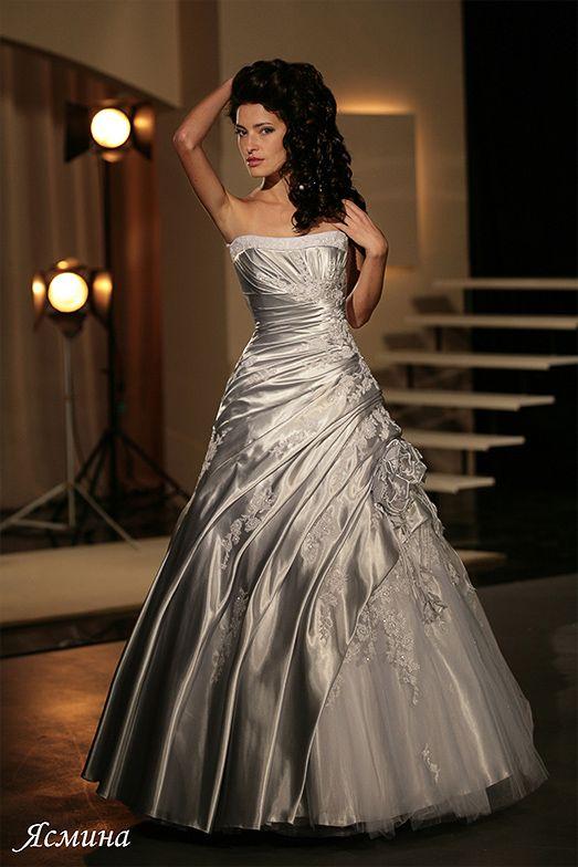 Свадебное платье пышного кроя из глянцевого атласа, украшенное вышивкой и драпировками.