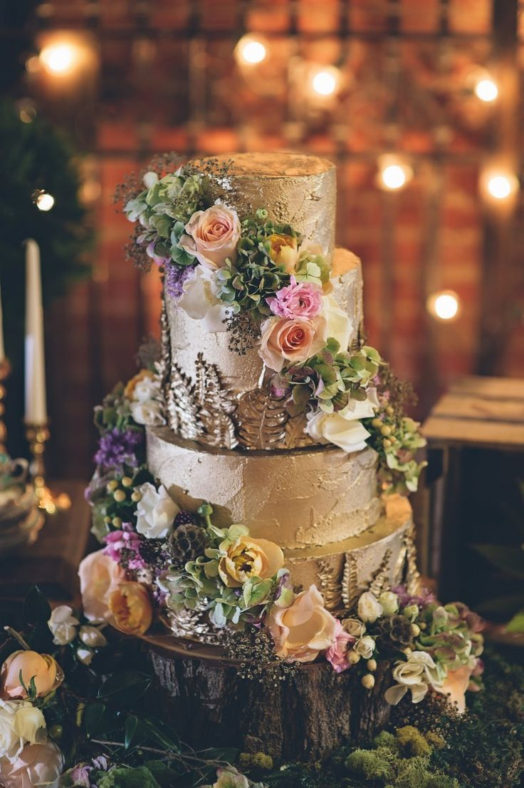 a gold wedding cake with perfect flora and fauna!