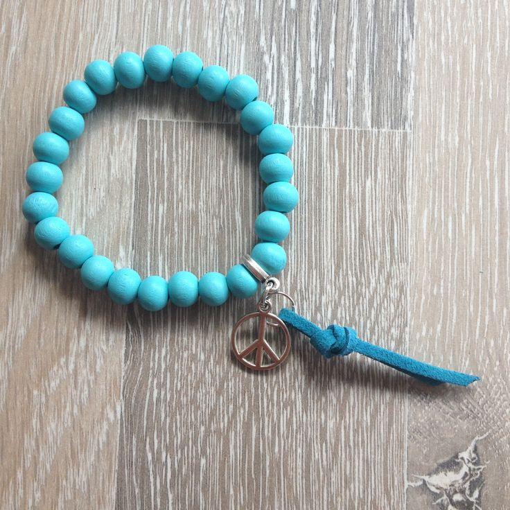 Armband van 8mm licht blauw hout met metalen peace en blauwe suède ribben. Van JuudsBoetiek, €3,50. Te bestellen op www.juudsboetiek.nl.