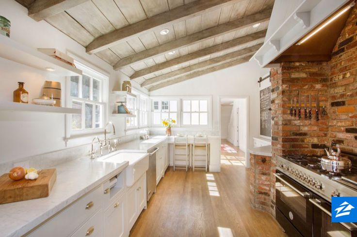 From the brick wall to the light wood ceilings -- this sunny kitchen is farmhouse perfection.
