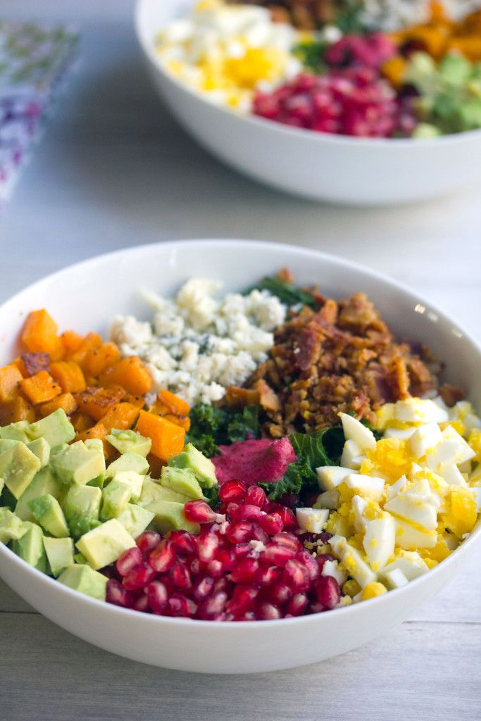 This recipe for a fall-inspired cobb salad is packed with kale, avocado, egg, pomegranate, bacon, squash, and gorgonzola cheese, plus a cranberry dressing.