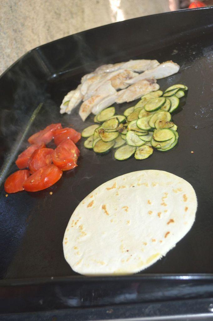 Tortilla au poulet et légumes grillés à la plancha Il vous faudra pour 4 à 6 tortillas:      250 g de farine     40 g de beurre pommade     1 càc de sel     1/2 càc de levure chimique     5 cl d'eau     5 cl de lait     deux escalopes de poulet     une petite courgette     deux tomates     de la salade
