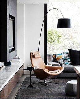 Scaun rotativ din piele si lampa de podea asezate in living pentru citit