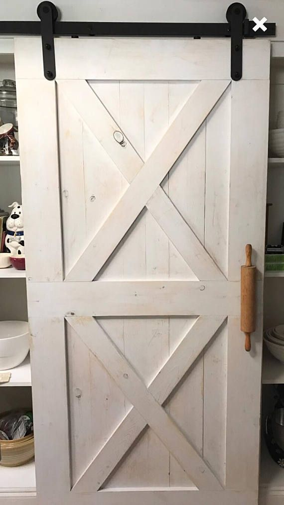 I love this farmhouse door. Check out the rolling pin handle. Farmhouse style barn door. #farmhouse #barn #door #farmhousestyle #ad