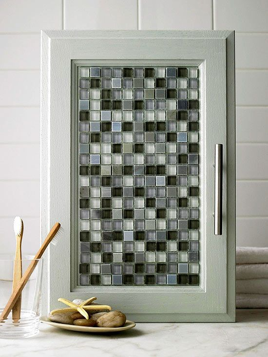 After you've primed and painted your cabinets, add a little sparkle with tile. Lay out and trim mesh-back glass tile to fit the door panel. Apply tile adhesive to the door with a putty knife and adhere the tiles. You don't need to grout the tile, but if you do, be sure the cabinet hinges are strong enough to hold the extra weight of the grout.