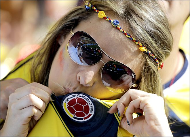 A Colombian supporter kisses her shirt badge as she celebrates after the group C World Cup soccer match between Colombia and Ivory Coast at the Estadio Nacional in Brasilia, Brazil, Thursday, June 19, 2014. Colombia won the match 2-1. (AP Photo/Sergei Grits)
