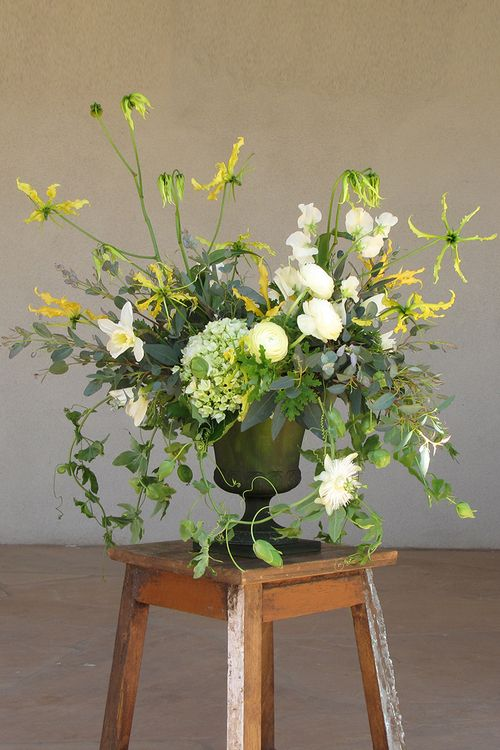 Garden centerpiece by Cincinnati wedding florist Floral Verde LLC.  Centerpiece contains ivory sweet peas, ivory ranunculus, ivory daffodils, yellow gloriosa lily, green hydrangea, scented geranium, gunnii eucalyptus and passion vine, arranged in a vintage green urn. Switch out whites for oranges and pinks...