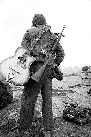 Carrying a guitar and a M16 rifle, a Marine waits at a landing strip for a flight out of Khe Sanh, February 25th, 1968.  It was the era of Rock & Roll and more people turned up for James Brown at the yearly USO extravaganza, than for Bob Hope.