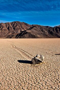 Sailing stones, sliding rocks, and moving rocks all refer to a geological phenomenon where rocks move in long tracks along a smooth valley floor, known as Racetrack Playa, without human or animal intervention.