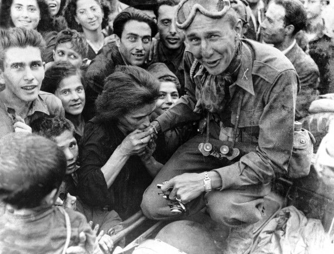 An Italian woman kisses the hand of a soldier of the U.S. Fifth Army after troops move into Naples in their invasion and advance northward in Italy, on October 10, 1943. (AP Photo)