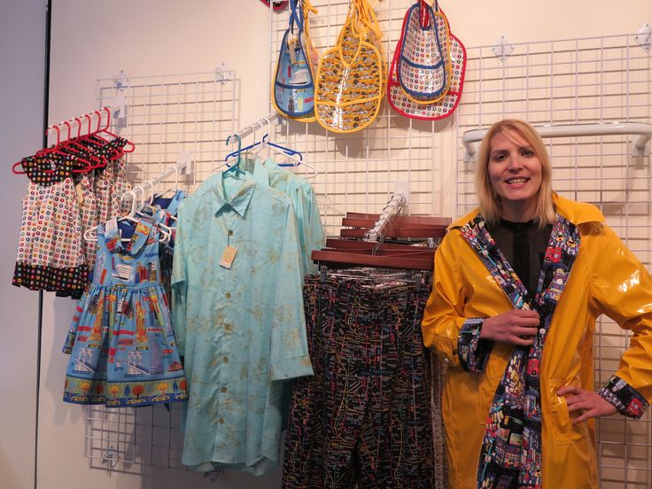 CQ Staffer Karen standing in the NYC Boutique section of The City Quilter while wearing a NYC Boutique raincoat lined with The City Quilter's exclusive Times Square Print.