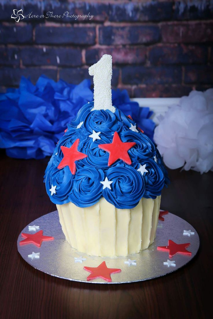 A red, white and blue Giant Cupcake with edible topper for a little boy's cake smash session. Photo courtesy of Here Or There Photography.