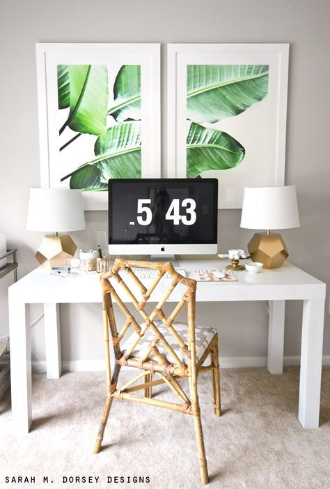 Tropical leaf wall art, in a clean workspace, with a bamboo chair.