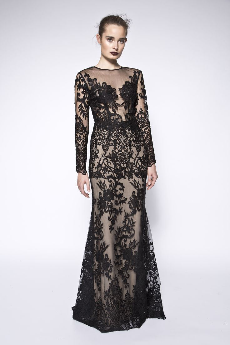 Lace embellished gown. The Milla dress is a black sheer gown carefully embellished with lace. This gown feature long lace embellished sleeves, has a rounded neckline but gives off the illusion of a V neckline. It is designed as a slim fit but gradually flares at the mid thigh. This look has a delicate and stunning feel. #evening #floral #lace #sleeves #specialoccasions