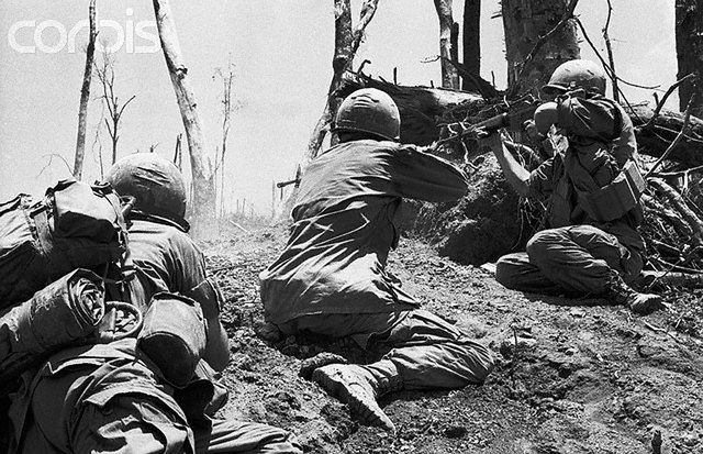 """3/20/1969-A Shau Valley, South Vietnam: Two members of the 101st Airborne Division fire into a North Vietnamese bunker near the top of """"Hamburger Hill"""" overlooking the A Shau Valley.  The paratroopers captured the summit of the hill 5/20 after 11 assaults in 10 days that killed or wounded more than 300 U.S. soldiers. --- Image by © Bettmann/CORBIS"""