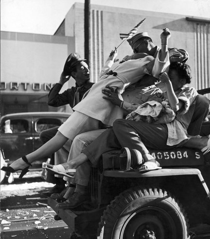 """Caption from the August 27, 1945, issue of LIFE. """"On Hollywood Boulevard in Los Angeles carousing servicemen neck atop the hood of a careening jeep. The city rocked with joy as impromptu pedestrian parades and motor cavalcades whirled along, hindered only by hurled whiskey bottles, amorous drunks and collisions."""""""