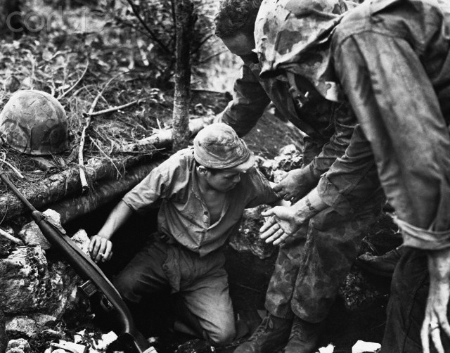 Marines help a Japanese soldier from a dugout on Tinian Island during the Fall of Tinian in World War II. He holds a cigarette the Leathernecks used to coax him out.
