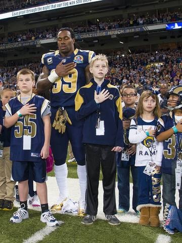St. Louis Rams running back Steven Jackson (39) stands with children for a moment of silence for the victims in the Newtown, Conn. school shooting before the game against the Minnesota Vikings at the Edward Jones Dome.  Scott Rovak, USA TODAY Sports
