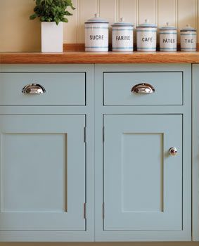 I love the simplicity of these Shaker style doors, the nickle cup pulls, and the bead board back splash. It is also a wonderful blue. Bravo to the designer!