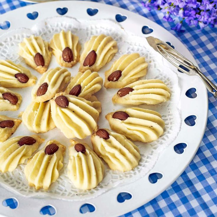 Spritsade klassiska småkakor som dekoreras med en sötmandel.