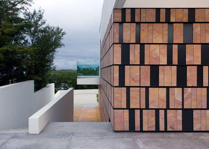 Volcanic stone wall hides doorway into B25 house by PK Arkitektar