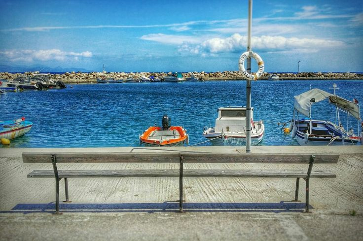 A place to sit and watch the boats at Kavos harbour at Psarou on Zakynthos island Greece Photography by Alistair Ford