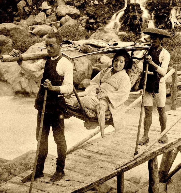Smiling lady in a kago (sedan chair) crossing a wooden bridge. 1904. Japan