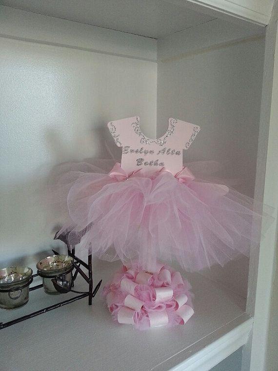Actualmente estamos fuera el adorno del Applique de astilla y sustituirla con perlas *** Este centro de mesa de tutu vestido (bailarina) hará un acento hermoso a su bailarina evento temático y cuenta con dos caras. También coordina muy bien con nuestras tartas de pañales de bailarina. Está parado aproximadamente 13 1/2 pulgadas de alto en un tablero de espuma base que está cubierta con rollos de cartulina de alta calidad color rosa y tul rosa. El vestido fluye maravillosamente con tul ...