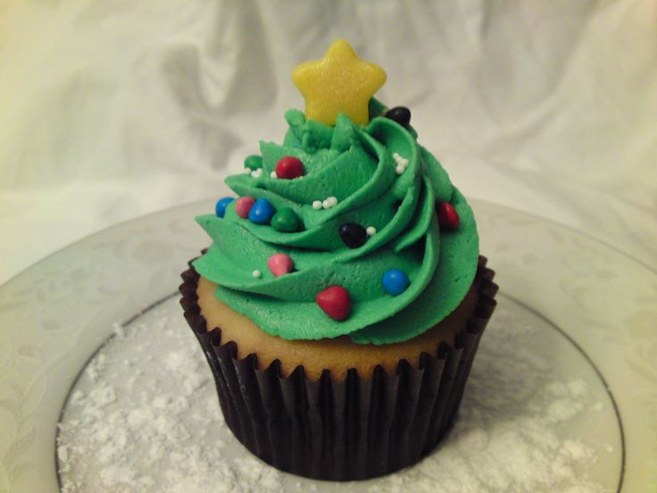 "Christmas tree cupcake - White cake with vanilla buttercream.  ""Tree"" piped with Wilton tip 1M.  ""Lights"" are Wilton rainbow chips and white nonpareils.  The star is fondant dusted with yellow luster dust  :)"