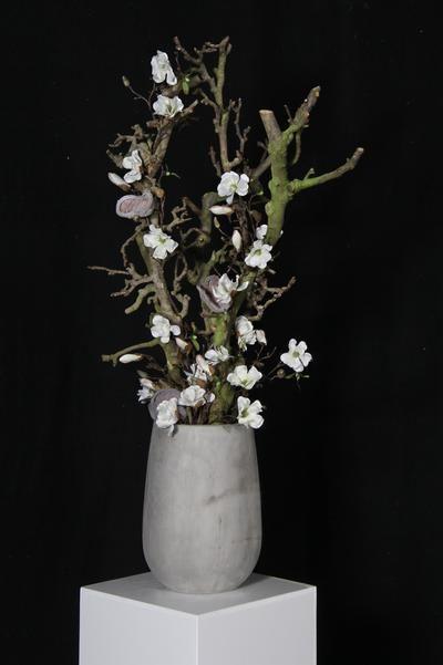 Betonnen vaas met decoratietakken en zijde bloemen. makkelijk en mooi