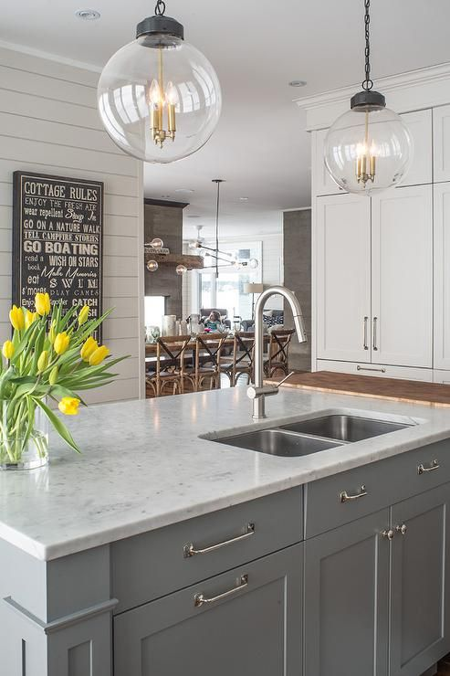 Two Regina Andrew Large Globe Pendants illuminate a gray kitchen island topped with white marble fitted with a stainless steel dual sink and gooseneck faucet.