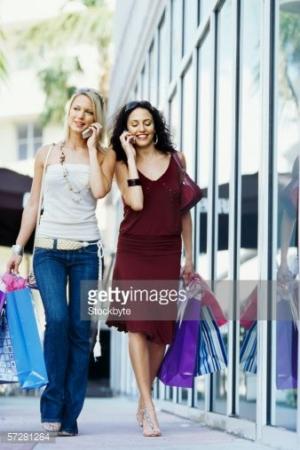 Stockfoto : Young women walking and talking on mobile phones