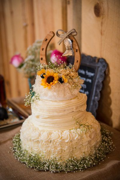 Country wedding cake idea - three-tiered wedding cake with sunflowers, baby's breath + horseshoe cake topper {Tanna White Photography}