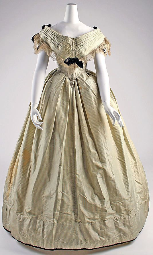 Finely striped evening dress, likely silk, British, ca 1855-60. Pointed bodice, short sleeves, pleated bertha, box pleated skirt.Trimmed with velvet and lace. MET